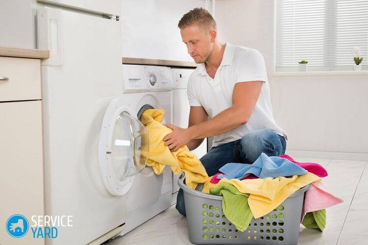 Man Putting Dirty Clothes Into The Washing Machine
